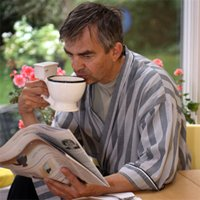 Man drinking from a toilet bowl-shaped coffee cup